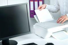 L'homme met la pile de papier dans l'imprimante image stock