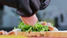 L'homme met le jambon sur le pain avec de la laitue tout en faisant cuire le sandwich banque de vidéos