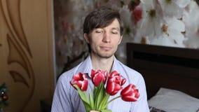 L'homme met un doigt à ses lèvres, obtient des fleurs - des tulipes et puis cligne de l'oeil banque de vidéos