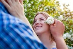 L'homme met une fleur dans ses cheveux du ` s d'amie Couples heureux détendant au printemps le jardin Photographie stock