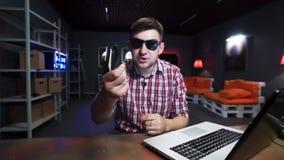 L'homme mignon avec des lunettes de soleil parle à la caméra et jette deux portefeuilles avec l'argent banque de vidéos