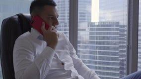 L'homme mignon de brune dans la chemise blanche parle du smartphone dans le bureau moderne banque de vidéos