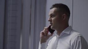 L'homme mignon de brune dans la chemise blanche parle du smartphone près de la fenêtre dans le bureau banque de vidéos