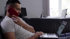 L'homme mignon de brune dans le T-shirt gris parle du smartphone s'étendant sur le sofa clips vidéos