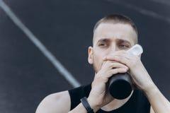 L'homme mince musculaire dans la formation aux boissons de stade arrosent d'un dispositif trembleur de sports sports de r?cr?atio image libre de droits