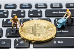 L'homme miniature creusent les bitcoins d'or de extraction Photo stock