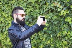 L'homme moderne et avec la barbe prennent une photo Photographie stock