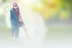 L'homme mol de foyer embrumant pour éliminer le moustique pour empêchent la fièvre dengue de diffusion Photo stock