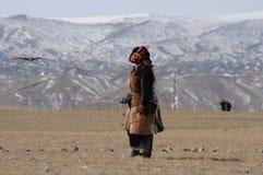 L'homme mongol kazakh s'est habillé avec l'équipement traditionnel formant l'aigle d'or pour attraper un renard prient photo stock