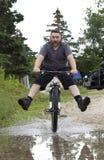 L'homme monte le vélo par le magma/ Photo libre de droits