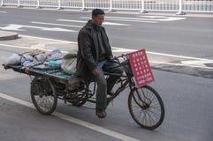 L'homme monte sur le tricycle de fret dans la scène de rue Images stock