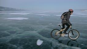 L'homme monte une bicyclette sur la glace Le cycliste est habillé dans une veste, un sac à dos et un casque de gris vers le bas G clips vidéos