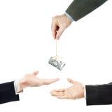 L'homme montre des autres hommes du doigt avec un paquet de dollars dans le fil Image stock
