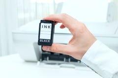 L'homme montre la cartouche à l'encre noire image stock