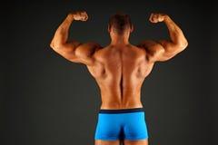 L'homme montre le sien arrière Image stock