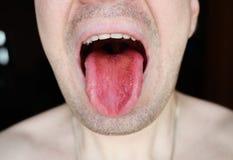 L'homme montre sa langue images stock