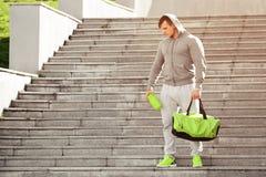 L'homme musculaire actif de sport tenant le dispositif trembleur et les sports mettent en sac, dehors images stock