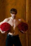 L'homme musculaire barbu avec le corps sexy tient la boîte de rose de rouge Photo libre de droits
