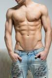 L'homme musculaire dans des jeans déchirés se tient près du sofa Image libre de droits