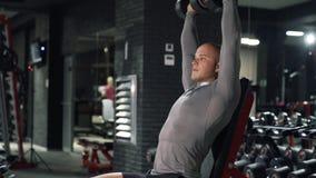 L'homme musculaire fort en gros plan s'exerce dans le gymnase foncé L'athlète s'assied sur un banc et des haltères de presses, tr clips vidéos