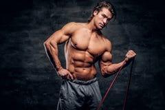 L'homme musculaire puissant fait des exercices avec le caoutchouc et montre ses muscules photographie stock libre de droits