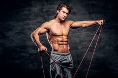 L'homme musculaire puissant fait des exercices avec le caoutchouc et montre ses muscules photo libre de droits