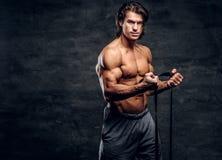 L'homme musculaire puissant fait des exercices avec le caoutchouc et montre ses muscules image libre de droits