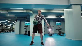L'homme musculaire soul?ve le kettlebell lourd au-dessus de sa t?te dans le gymnase lumineux dans le mouvement lent clips vidéos
