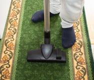 L'homme nettoie à l'aspirateur le tapis photographie stock libre de droits