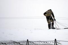 L'homme nettoie la neige du toit de la maison illustration de vecteur
