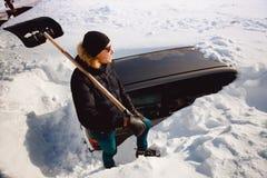 L'homme nettoie la neige et nettoie la pelle à voiture de la neige image libre de droits