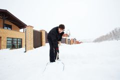 L'homme nettoie la pelle à neige Photo stock
