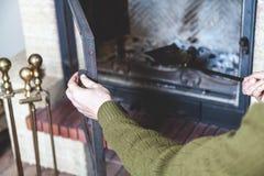 L'homme nettoie la pelle en laiton à cheminée Photographie stock libre de droits