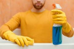 L'homme nettoie la salle de bains avec des produits d'éponge et d'entretien images stock