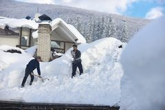 L'homme nettoie le toit de la maison pendant des chutes de neige photo stock