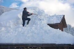 L'homme nettoie le toit de la maison pendant les chutes de neige 2017 images libres de droits