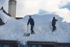 L'homme nettoie le toit de la maison pendant les chutes de neige 2017 images stock