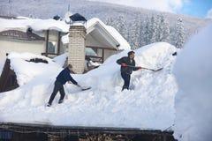 L'homme nettoie le toit de la maison pendant les chutes de neige 2017 photographie stock