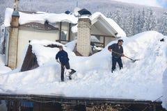 L'homme nettoie le toit de la maison pendant les chutes de neige 2017 photo stock