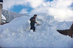 L'homme nettoie le toit de la maison pendant les chutes de neige 2017 photo libre de droits