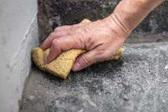 L'homme nettoie les joints frais de mortier Images libres de droits