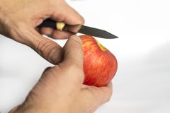 L'homme nettoie, pomme rouge de coupes photos stock