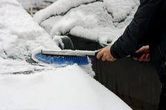L'homme nettoie une voiture de la neige Photo stock
