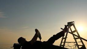 L'homme non de finition de travail se reposant dans la pile des outils silhouettent le tir panoramique banque de vidéos