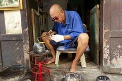 L'homme non identifié font le baht, l'aumône roulent utilisé par des moines pour recevoir des donations des nourritures photo libre de droits