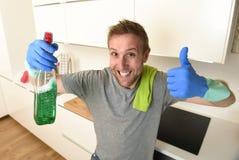 L'homme non rasé heureux dans les gants de lavage en caoutchouc tenant le nettoyage détersif pulvérisent le sourire sûr photos libres de droits