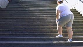 L'homme obèse montant des escaliers, poids excessif cause la douleur dans les joints, veines variqueuses banque de vidéos