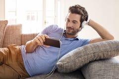 L'homme observe à la maison un film au téléphone portable Photographie stock