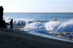 L'homme observe la vague déferlante de broyage Image libre de droits