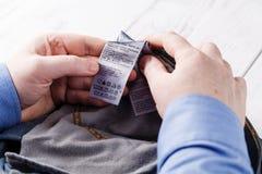 L'homme observe les instructions pour les vêtements de lavage photos stock